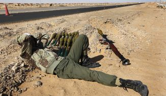 A Libyan anti-government rebel lies by the roadside at an advance checkpoint between the town of Ras Lanouf and Bin-Jawad, eastern Libya, Monday, March 7, 2011. An air strike hit Ras Lanouf, a key oil port held by the rebels, on Monday but there were no casualties. A day earlier, a heavy assault by pro-regime forces stalled the rebel advance. (AP Photo/Hussein Malla)