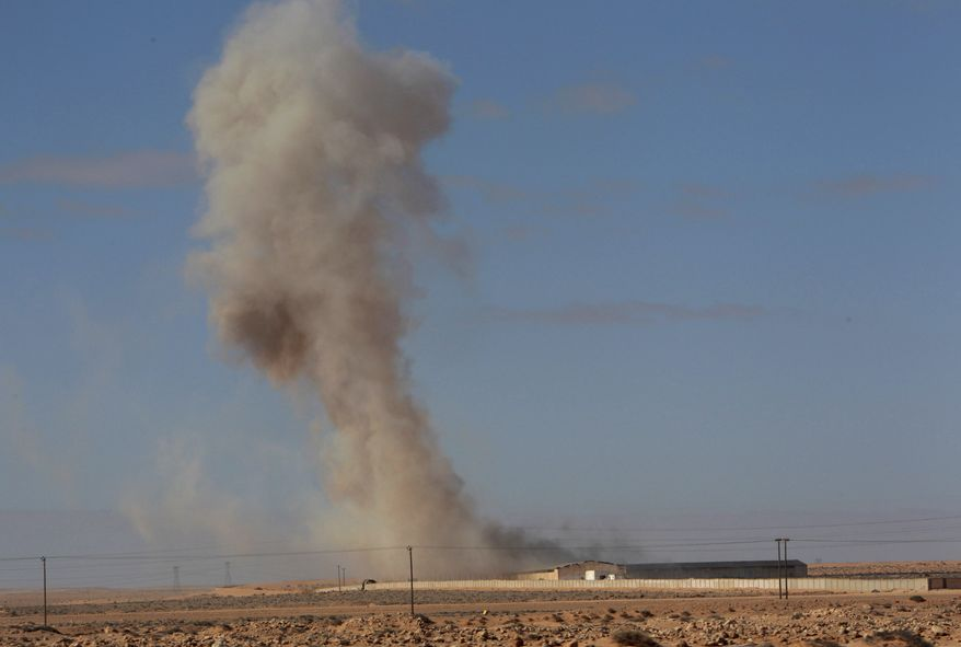 Smoke raises from a military army base that fell to the rebels opposed to Libyan leader Col. Moammar Gadhafi following an airstrike by Libyan warplanes that attacked in the oil town of Ras Lanouf, in eastern Libya, on Sunday, March 6, 2011. The anti-Gadhafi rebels fared better elsewhere, capturing the key oil port of Ras Lanouf from regime forces on Friday night, their first military victory in a potentially long and arduous westward march from the east of the country to Tripoli, the capital. (AP Photo/Hussein Malla)