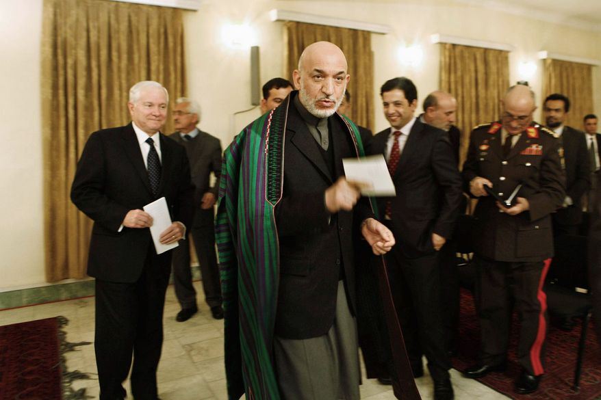 STAYING?: Secretary of Defense Robert M. Gates (left) and Afghan President Hamid Karzai discussed a pullout date for U.S. troops on Monday. Mr. Gates said some forces could stay after the 2014 pullout goal. (Associated Press)