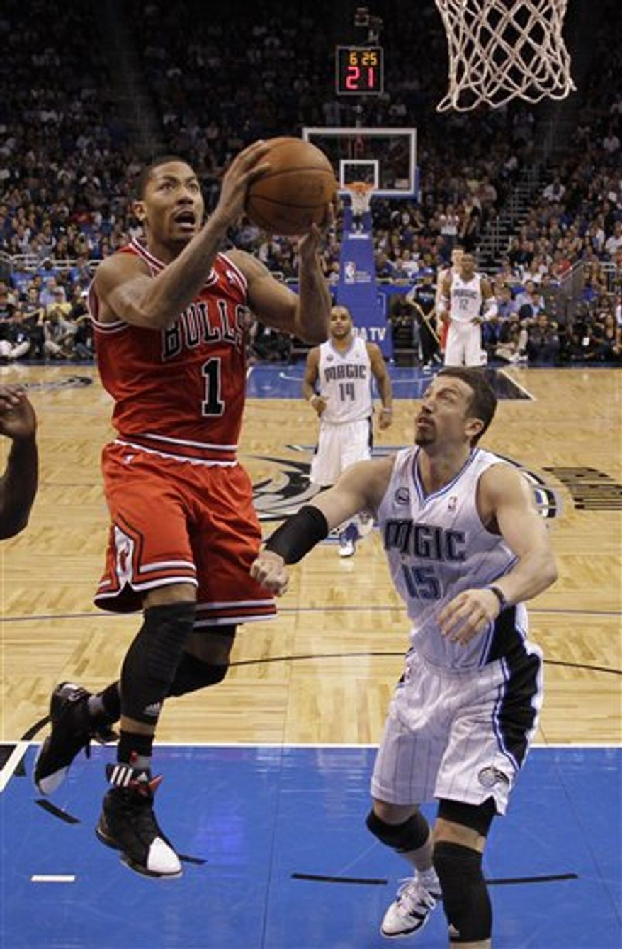 Chicago Bulls' Derrick Rose (1) goes in for a shot past Orlando Magic's Ryan Anderson during the first half of an NBA basketball game in Orlando, Fla., Sunday, April 10, 2011. (AP Photo/John Raoux)