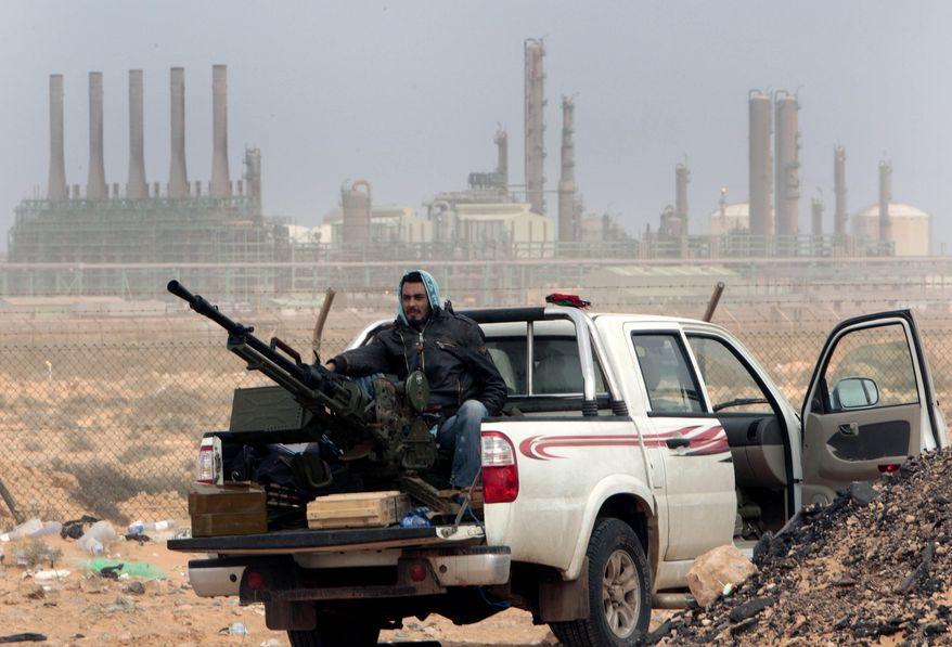 An anti-government rebel sits with an anti-aircraft weapon in front an oil refinery, after the capture of the oil town of Ras Lanouf, eastern Libya, on March 5, 2011. Oil prices climbed to near $107 a barrel Monday as intense fighting between Libyan government forces and rebels appeared to be turning into a civil war and raised the prospect of a prolonged cut in crude exports from the OPEC nation. (AP Photo/Hussein Malla, File)
