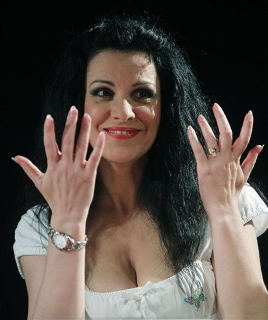 """FILE - In this July 20, 2010 file photo, Romanian soprano Angela Gheorghiu  gestures during news conference with at the Royal Opera House in Madrid.  The Met announced Monday, March 7, 2011, that Gheorghiu had pulled out of the Des McAnuff """"Faust"""" for """"artistic reasons.""""  (AP Photo/Paul White, file)"""