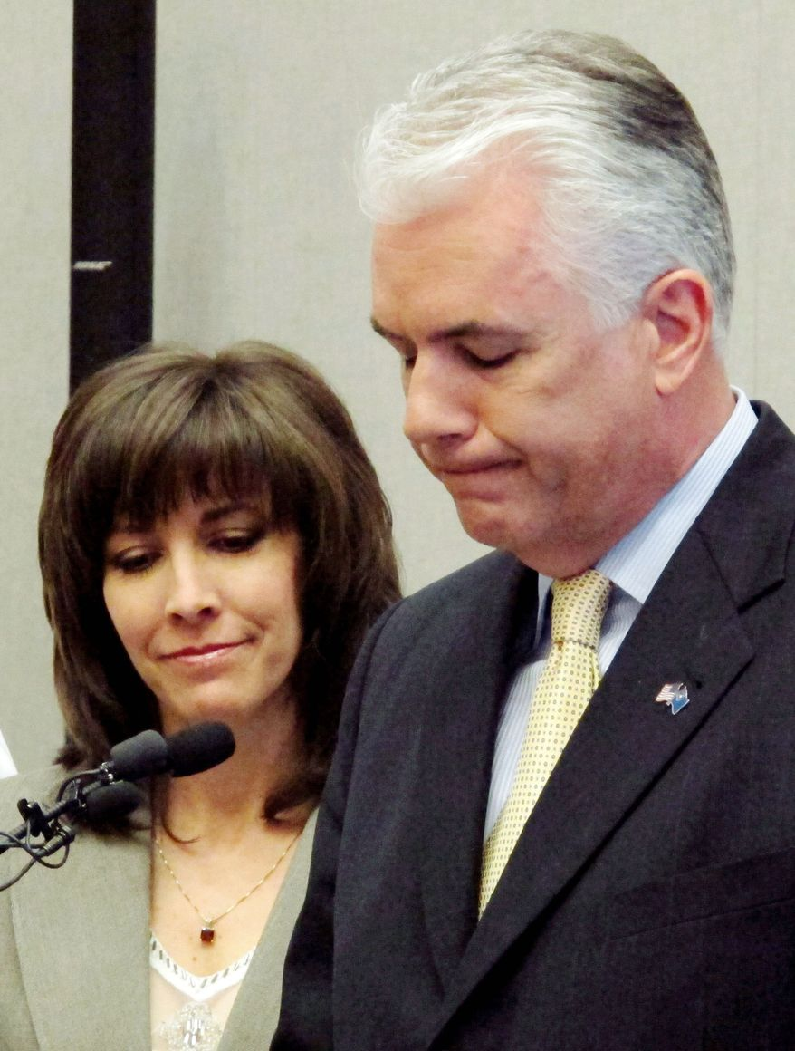 "Sen. John Ensign, Nevada Republican, accompanied by his wife, Darlene, announces he will not run for a third term at a news conference Monday in Las Vegas. He called it ""the most difficult decision that I have ever made."" (Associated Press)"