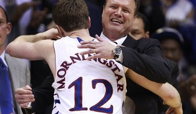 Kansas coach Bill Self, left, pats the head of senior guard Tyrel Reed (14) during the second half of an NCAA college basketball game in Lawrence, Kan., Wednesday, March 2, 2011. No. 2 Kansas defeated NO. 24 Texas A&M 64-51. Reed had 12 points. (AP Photo/Orlin Wagner)
