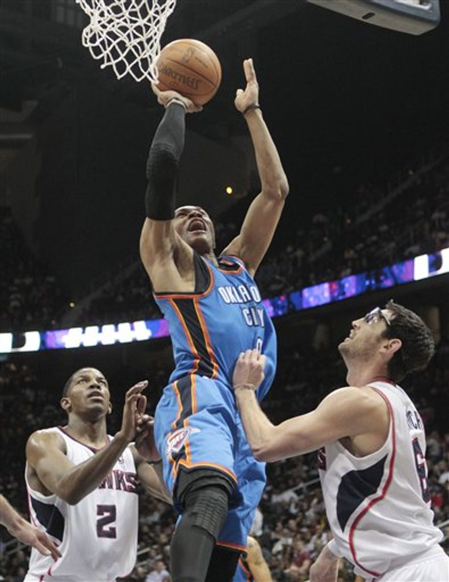 Oklahoma City Thunder point guard Russell Westbrook (0) goes between Atlanta Hawks'  Joe Johnson (2) and Zaza Pachulia (27), right, to score in the fourth quarter of an NBA basketball game in Atlanta, Friday, March 4, 2011. Oklahoma City  won 11-104 .(AP Photo/John Bazemore)