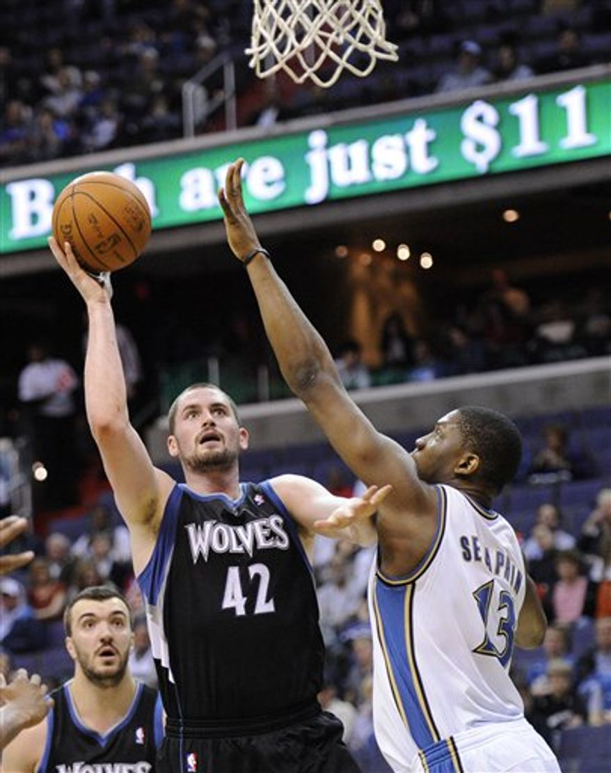 Minnesota Timberwolves forward Kevin Love (42) goes to the basket against Washington Wizards forward Kevin Seraphin, right, of French Guiana, during the first half of an NBA basketball game, Saturday, March 5, 2011, in Washington. (AP Photo/Nick Wass)