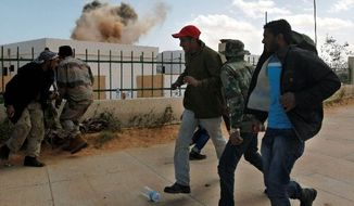 Rebels run as smoke rises from a house hit during an airstrike Tuesday in the oil port of Ras Lanouf in eastern Libya. Warplanes kept up attacks to prevent the opposition from advancing toward leader Col. Moammar Gadhafi's stronghold in the capital of Tripoli. (Associated Press)