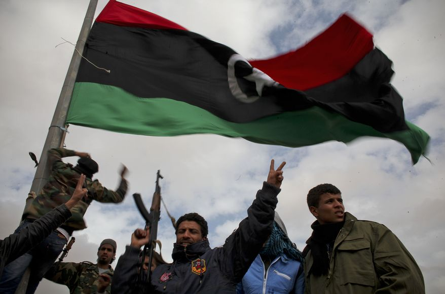 Libyan volunteers gesture as they raise a pre-Gadhafi flag on the outskirts of the eastern town of Ras Lanouf, Libya, on Tuesday, March 8, 2011. Forces loyal to Col. Moammar Gadhafi have scored a significant victory, recapturing the closest city to the capital to have fallen in rebel hands. (AP Photo/Tara Todras-Whitehill)