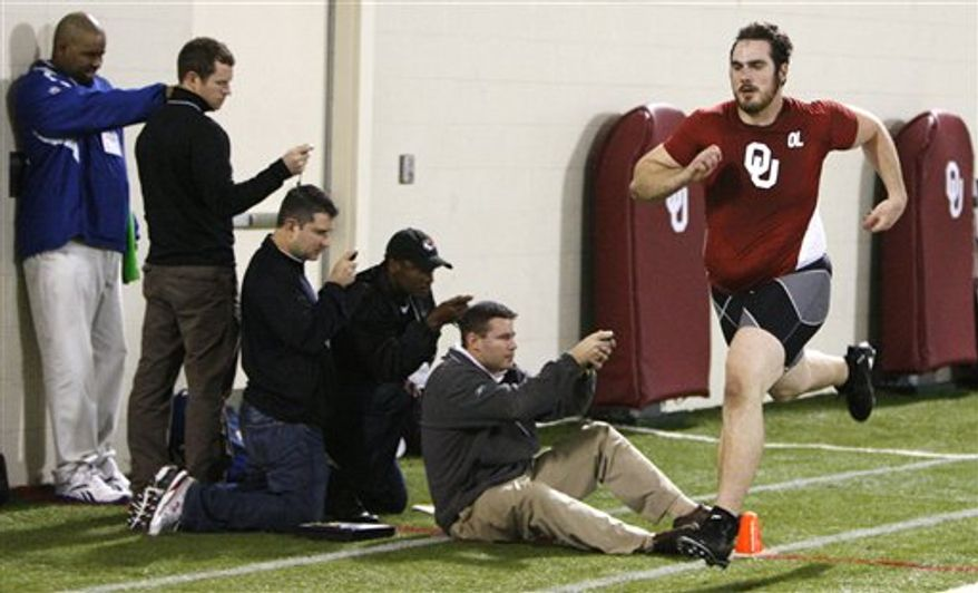 Joe Greene, center, of the Pittsburgh Steelers, and Jack Glowik, right, of the Baltimore Ravens, time players in the 40-yard dash at Oklahoma Pro Day for NFL scouts in Norman, Okla., Tuesday, March 8, 2011. (AP Photo/Sue Ogrocki)