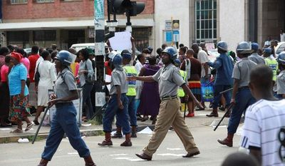 "Zimbabwean police move in to stop members of Women of Zimbabwe Arise from marching in Harare, Zimbabwe, on Feb. 15. Human Rights Watch said in a report that the country faces a ""crisis of impunity"" that encourages state-orchestrated killings, torture and beatings. (Associated Press)"