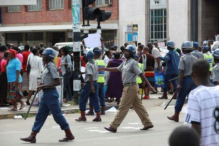 """Zimbabwean police move in to stop members of Women of Zimbabwe Arise from marching in Harare, Zimbabwe, on Feb. 15. Human Rights Watch said in a report that the country faces a """"crisis of impunity"""" that encourages state-orchestrated killings, torture and beatings. (Associated Press)"""