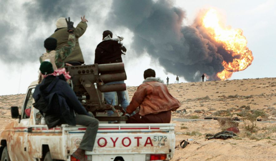 AFLAME: Anti-Gadhafi rebels transport a multiple-rocket launcher Wednesday as flames rise from a fuel-storage facility that was attacked in fighting with pro-Gadhafi forces, in Sedra, Libya. (Associated Press)