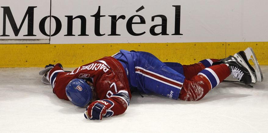 Montreal Canadiens' Max Pacioretty lays on the ice after taking a hit by Boston Bruins' Zdeno Chara during the second period of an NHL hockey game, Tuesday, March 8, 2011, in Montreal. (AP Photo/The Canadian Press, Paul Chiasson)