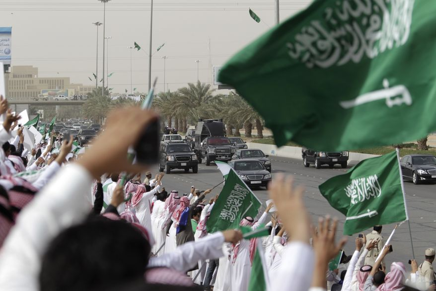 ** FILE ** Saudis wave and cheer to welcome Saudi King Abdullah as his convoy travels through the streets of Riyadh, Saudi Arabia, on Wednesday, Feb. 23, 2011. The king was returning to Riyadh, the Saudi capital, after a three-month absence for back surgery in New York and convalescence in Morocco. (AP Photo/Hassan Ammar)