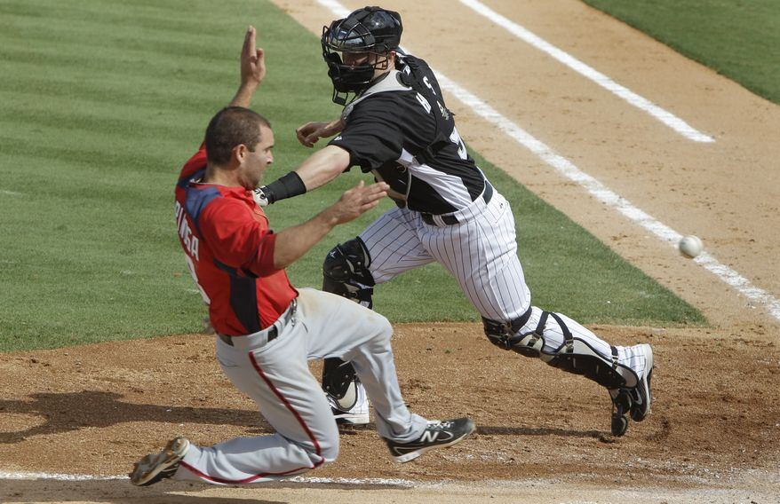 Washington Nationals' Danny Espinosa safely slides into home as Florida Marlins catcher Brett Hayes (9) misplays the relay during a spring training baseball game, Wednesday, March 9, 2011 in Jupiter, Fla. (AP Photo/Carlos Osorio)