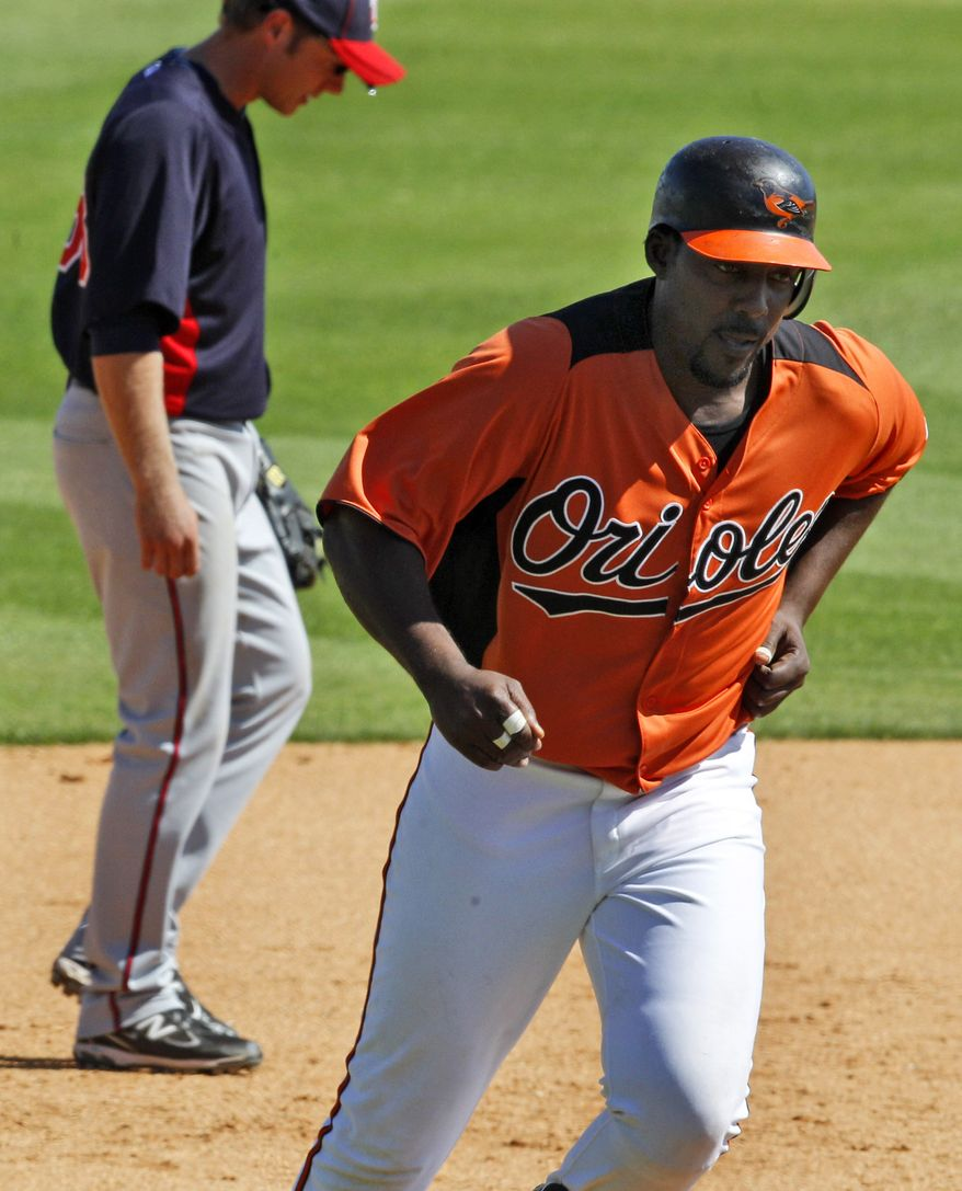 Baltimore Orioles' Vladimir Guerrero, right, rounds third past Minnesota Twins third baseman Luke Hughes after hitting a solo-homer in the fifth inning a spring training baseball game in Sarasota, Fla., Wednesday, March 9, 2011. (AP Photo/Gene J. Puskar)
