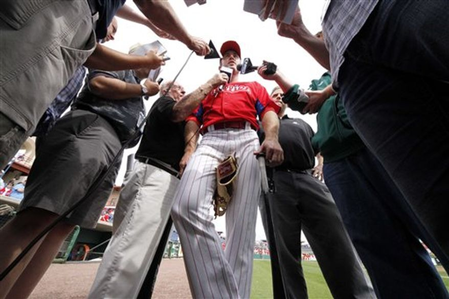 Philadelphia Phillies' Chase Utley, center, is interviewed after taking batting practice before a spring training baseball game against the Pittsburgh Pirates in Clearwater, Fla., Saturday, March 5, 2011. Utley did not play in the game. (AP Photo/Gene J. Puskar)