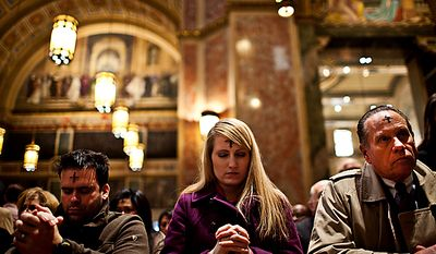 From left, Carlos Bonafonte, of Alexandria, Va., Christina Paschyn, of Washington, and Peter Terpeluk, of Washington, take part in prayer during Ash Wednesday Mass at the Cathedral of St. Matthew the Apostle, on Rhode Island Avenue in northwest Washington, Wednesday, March 9, 2011. (Drew Angerer/The Washington Times)