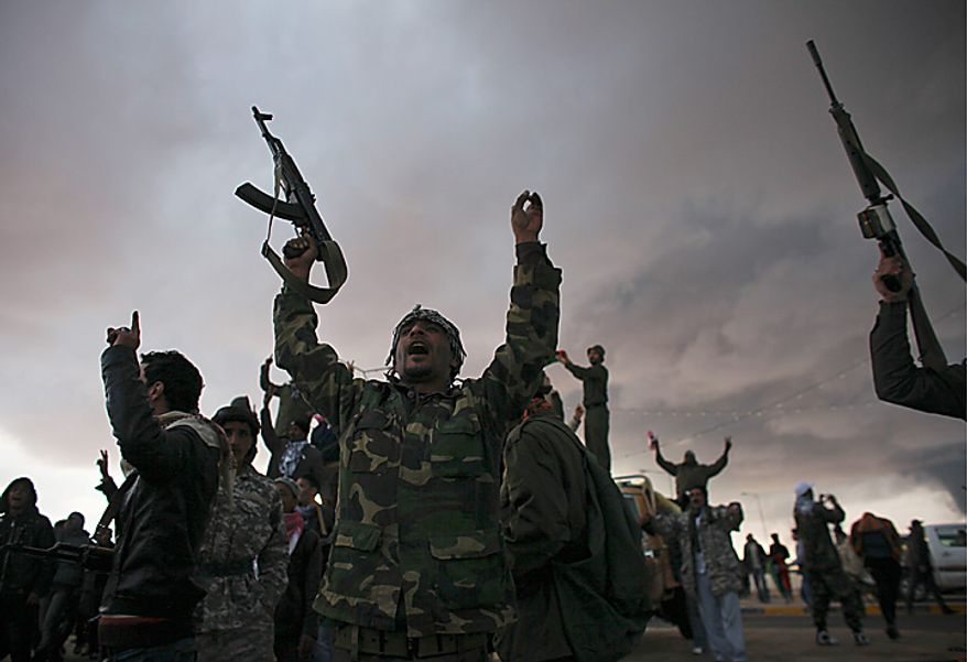 Libyan volunteers cheer as smoke rises from the oil port of Sidr in the background, in the eastern town of Ras Lanouf, Libya, Wednesday, March 9, 2011. A high-ranking member of the Libyan military flew to Cairo on Wednesday with a message for Egyptian army officials from Moammar Gadhafi, whose troops pounded opposition forces with artillery barrages and gunfire in at least two major cities. (AP Photo/Tara Todras-Whitehill)