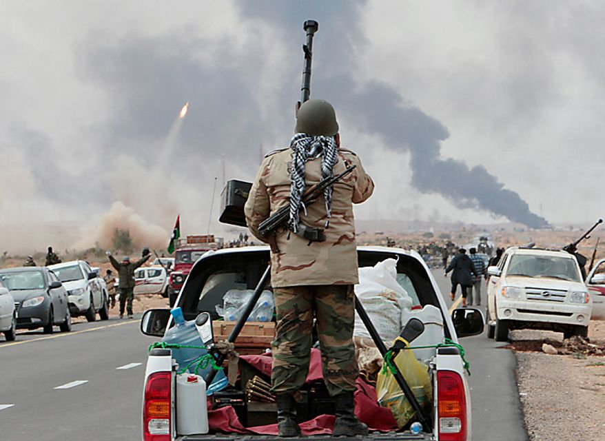 An anti-Gadhafi rebel stands behind his anti-aircraft gun, as other rebels fire rocket launchers, seen at left, during fighting against pro-Gadhafi fighters, in Sedra, eastern Libya, Wednesday March 9, 2011. A high-ranking member of the Libyan military flew to Cairo on Wednesday with a message for Egyptian army officials from Moammar Gadhafi, whose troops pounded opposition forces with artillery barrages and gunfire in at least two major cities. Col. Gadhafi appeared to be keeping up the momentum he has seized in recent days in his fight against rebels trying to move on the capital, Tripoli, from territory they hold in eastern Libya. (AP Photo/Hussein Malla)
