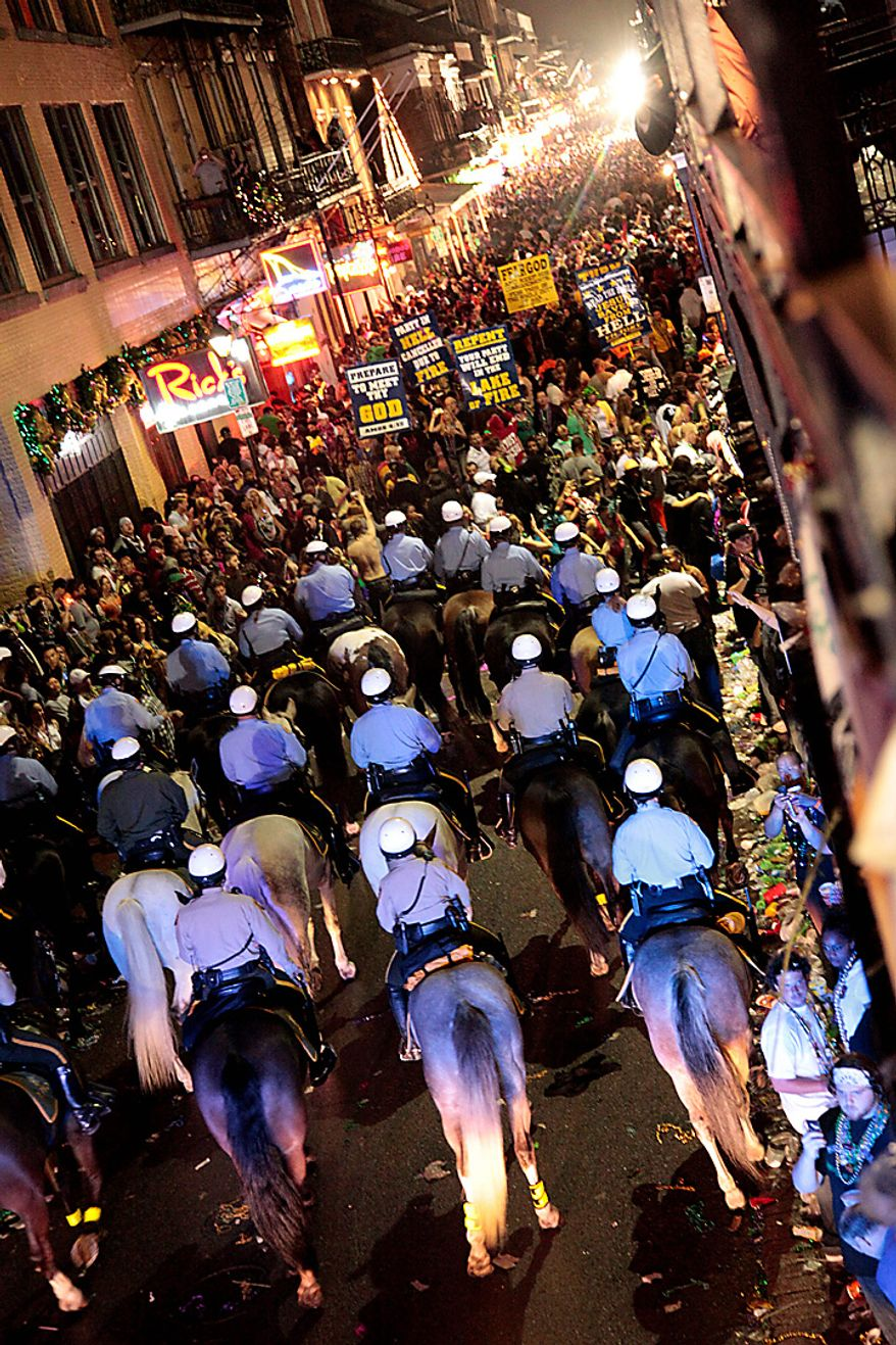 Police on horseback and foot clear out the crowds on Bourbon Street just after midnight for the end of Mardi Gras festivities in New Orleans Wednesday, March 9, 2011. (AP Photo/Gerald Herbert)