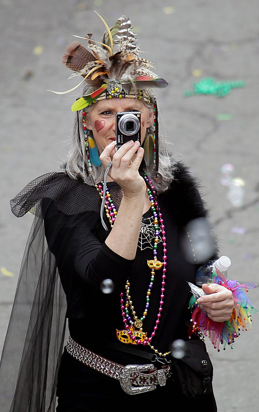 A costumed reveler takes a photograph at the Mardi Gras celebration in the French Quarter of New Orleans on Tuesday, March 8, 2011.  (AP Photo/Bill Haber)