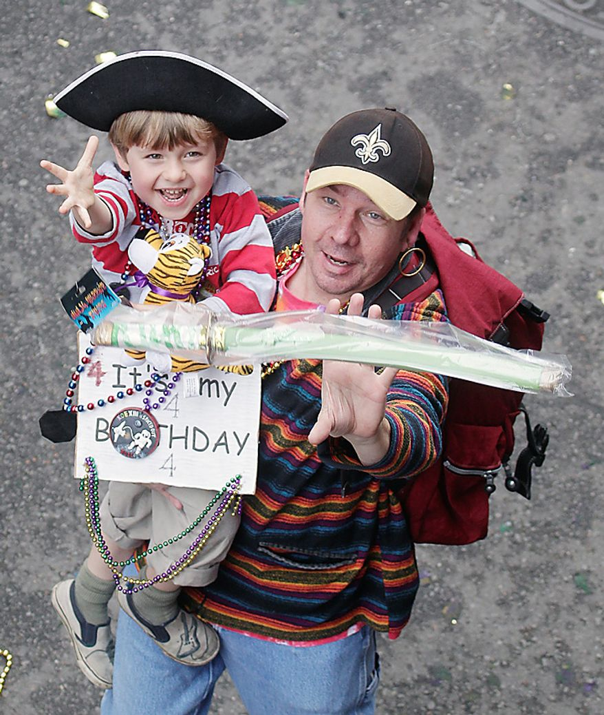 A young boy dressed as a pirate reaches to catch a plastic sword while enjoying the Mardi Gras celebration in the French Quarter of New Orleans, Tuesday, March 8, 2011.  (AP Photo/Bill Haber)