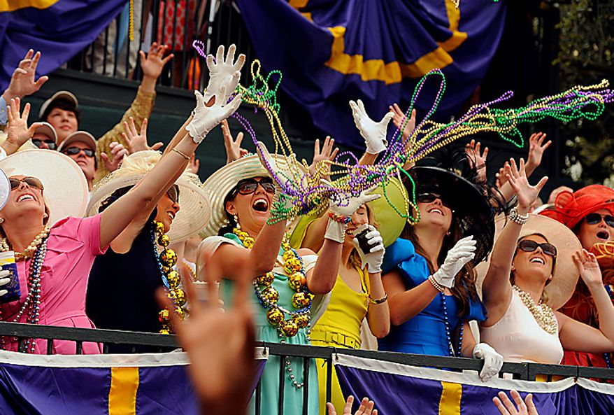 Members of King Felix III court toss beads to the crowds  gathered on Government Street in Mobile, Ala., Tuesday, March 8, 2011 for the pre-Lenten blowout along the Gulf Coast called Fat Tuesday.  (AP Photo/Press-Register, John David Mercer)