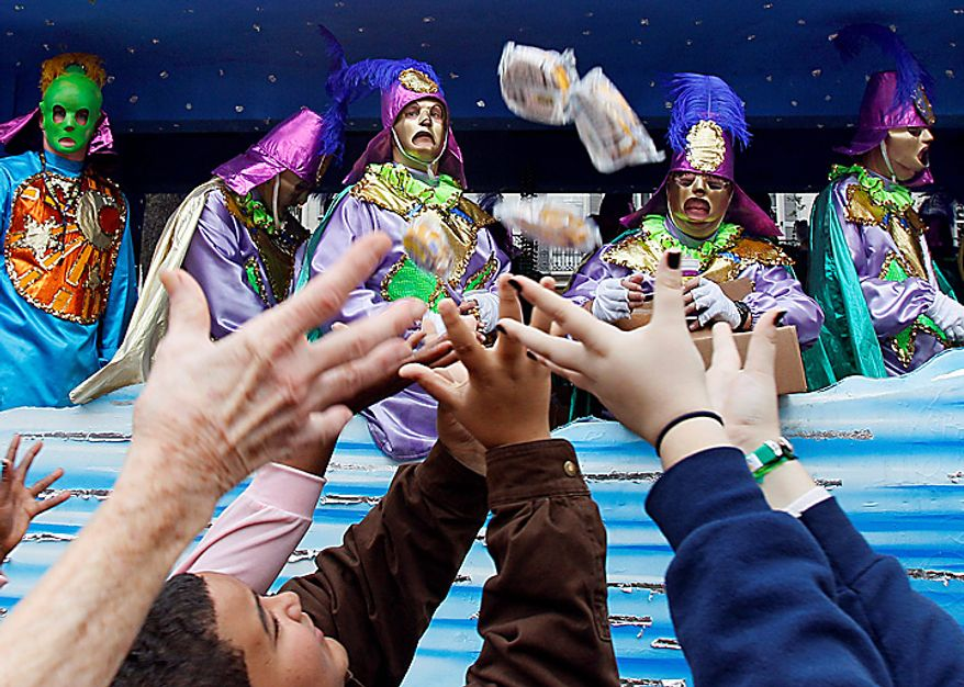 Revelers reach out for items thrown by riders on a float in the Rex parade as it makes its way down St. Charles Avenue in New Orleans on Mardi Gras Day, Tuesday, March 8, 2011. (AP Photo/Patrick Semansky)