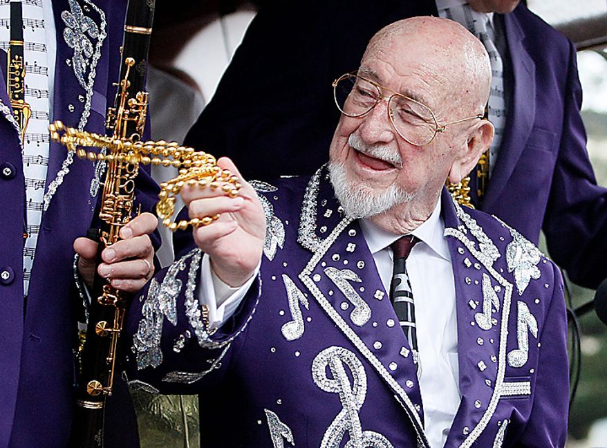 Musician Pete Fountain tosses beads to a reveler from a float as his Half-Fast Walking Club marches down St. Charles Avenue in New Orleans on Mardi Gras Day, Tuesday, March 8, 2011. (AP Photo/Patrick Semansky)