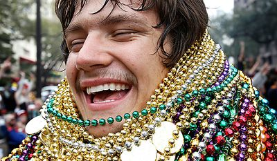 Lee Chance laughs as he shows off his collection of beads that he caught during the Zulu Social Aid and Pleasure Club parade in New Orleans on Mardi Gras Day, Tuesday, March 8, 2011. (AP Photo/Patrick Semansky)