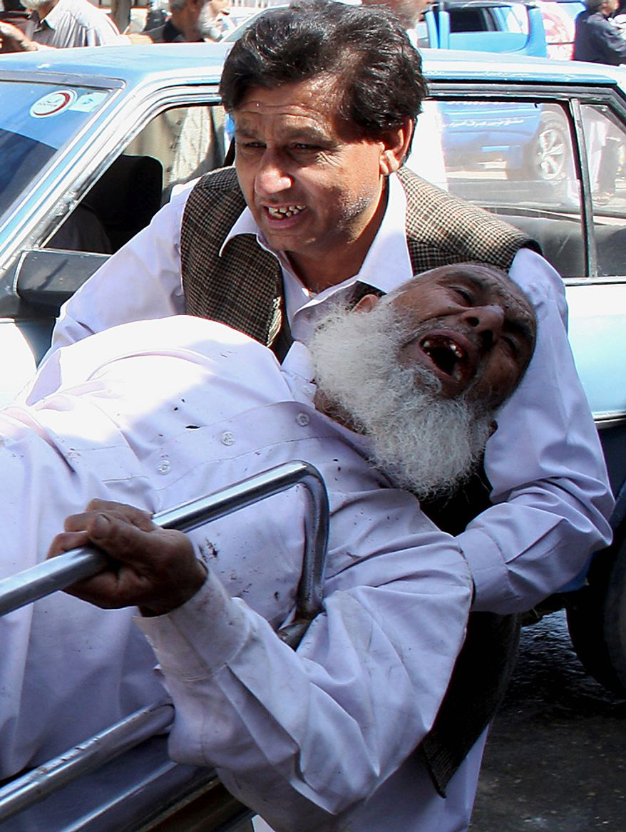 A man helps a person injured in a suicide attack, at a local hospital in Peshawar, Pakistan, on Wednesday, March 9, 2011. A suicide bomber attacked a funeral attended by anti-Taliban militiamen in northwest Pakistan killing many mourners and wounding more than 100 others, police said. (AP Photo/Mohammad Iqbal)