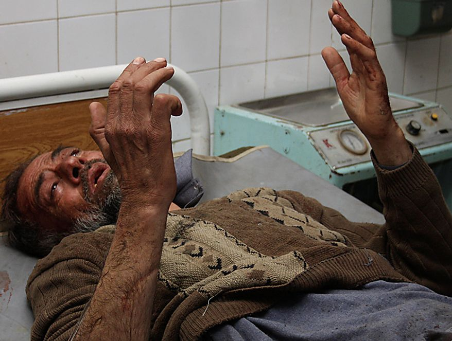 An injured man prays at a hospital bed in Peshawar, Pakistan, on Wednesday, March 9, 2011. A suicide bomber attacked a funeral attended by anti-Taliban militiamen in northwest Pakistan killing many mourners and wounding more than 100 others, police said. (AP Photo/Mohammad Iqbal)