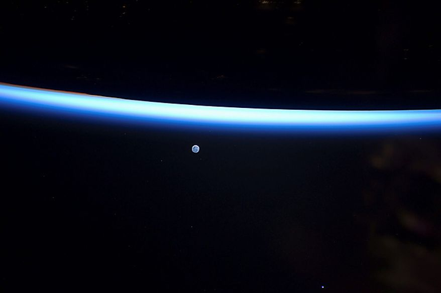 This image provided by NASA and photographed Sunday March 6, 2011, by an Expedition 26 crew member on the International Space Station shows Earth's thin line of atmosphere and a gibbous moon. (AP Photo/NASA)