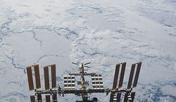 In this image provided by NASA the International Space Station is seen from Discovery backdropped against clouds over Earth, as the two orbital spacecraft accomplish their relative separation on March 7, 2011, after an aggregate of 12 astronauts and cosmonauts worked together for over a week. During a post undocking fly-around, the crew members aboard the two spacecraft collected a series of photos of each other's vehicle. Discovery ended its nearly 27-year flying career when it landed Wednesday. (AP Photo/NASA)