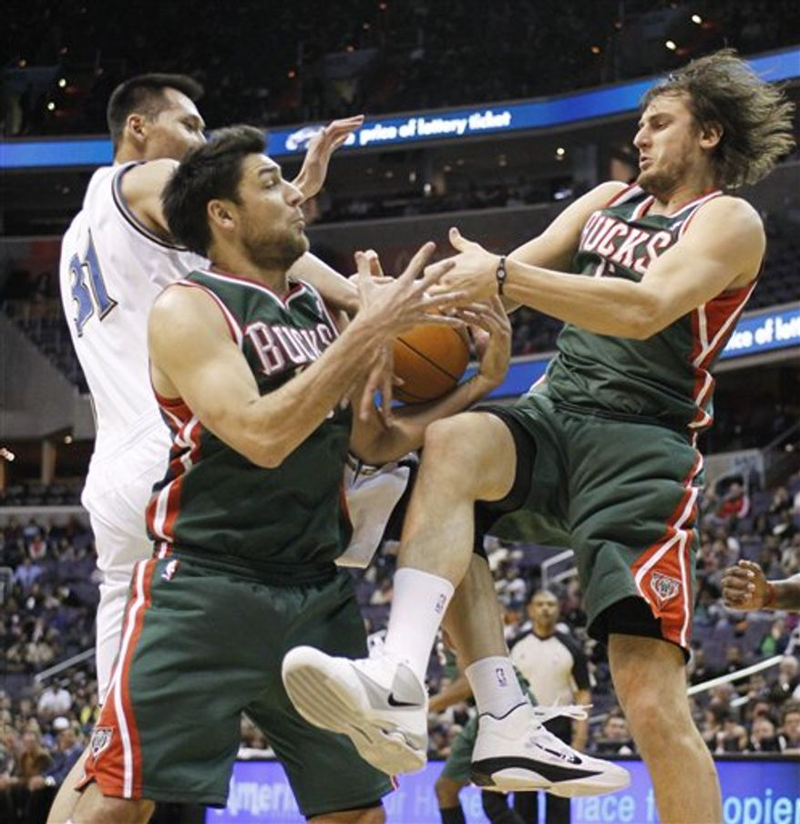 Milwaukee Bucks' Carlos Delfino, left, of Argentina, and Andrew Bogut, right, of Australia grab a rebound againstWashington Wizards' Yi Jianlian (31), of China, during the second half of NBA basketball game in Washington, Tuesday, March 8, 2011. Milwaukee won 95-76.  (AP Photo/Manuel Balce Ceneta)
