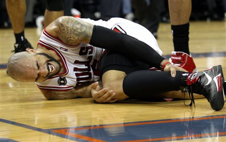 Chicago Bulls forward Carlos Boozer reacts after getting injured during the second half of an NBA basketball game against the Charlotte Bobcats, Wednesday, March 9, 2011, in Charlotte, N.C. Chicago won 101-84. (AP Photo/Nell Redmond)