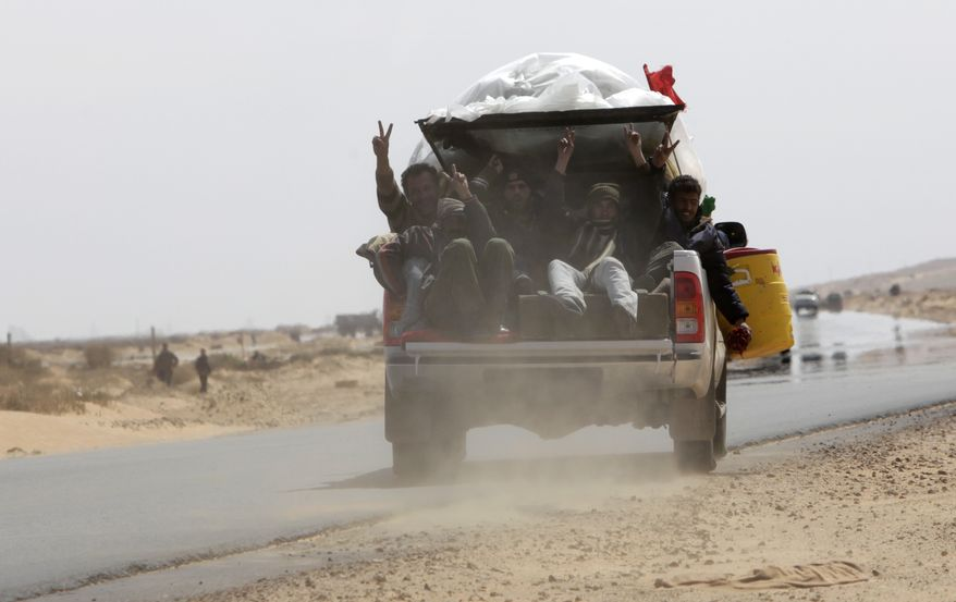 Libyan rebels fill the bed of a pickup truck leaving the eastern town of Ras Lanouf, Libya, on Thursday, March 10, 2011. Col. Moammar Gadhafi's forces pushed rebel fighters from the strategic oil port of Ras Lanouf on Thursday, driving the opposition from the city with a withering rain of artillery fire. (AP Photo/Nasser Nasser)