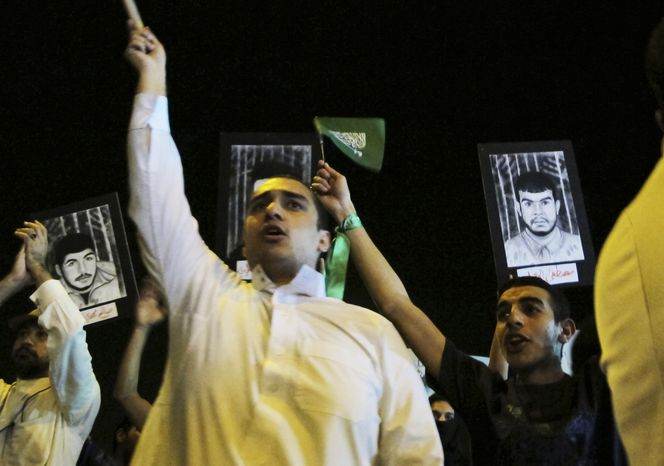 **FILE** Saudi Shi'ite protesters hold Saudi flags and portraits of unidentified Saudi Shi'ite prisoners during a demonstration in Qatif, Saudi Arabia, on March 9, 2011. Activists in Saudi Arabia's Shi'ite Mus