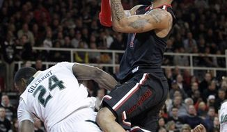 St. John's D.J. Kennedy, right, drives to the basket as he collides with South Florida's Augustus Gilchrist (24) during the second half of an NCAA college basketball game in New York, Saturday, March 5, 2011. St. Johns won 72-56. (AP Photo/Paul J. Bereswill)
