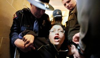 OUSTED: Elizabeth Wrigley-Field of Madison, Wis., is escorted out of the Wisconsin State Capitol Assembly Room lobby in Madison on Thursday after staying overnight with other demonstrators there. (Associated Press)