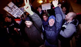 Demonstrators rush into the Wisconsin State Capitol Building after entering the building Wednesday evening, March 9, 2011. The Wisconsin Senate voted Wednesday night to strip nearly all collective bargaining rights from public workers, approving an explosive proposal that had rocked the state and unions nationwide after Republicans discovered a way to bypass the chamber's missing Democrats. (AP Photo/Wisconsin State Journal, John Hart)
