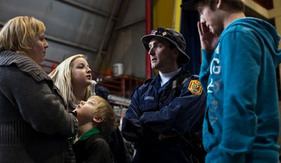 Tom Carver, a Fairfax County fireman from Bristow, talks with his family after packing up for the Fairfax Search and Rescue unit's mission to Japan, at the Fairfax Fire and Rescue Training Facility, in Fairfax, Friday, March 11, 2011. From left are, his wife Chrissy, daughter Haley, son Aden, and Kevin Whetzel. (Drew Angerer/The Washington Times)