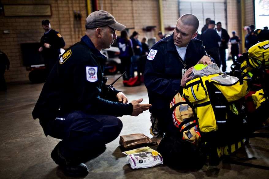 Brad Haywood, a Fairfax County firefighter, packs up his gear for the rescue mission in Japan as he talks to John MacDonald, left, at the Fairfax Fire and Rescue Training Facility, in Fairfax, Friday, March 11, 2011. (Drew Angerer/The Washington Times)