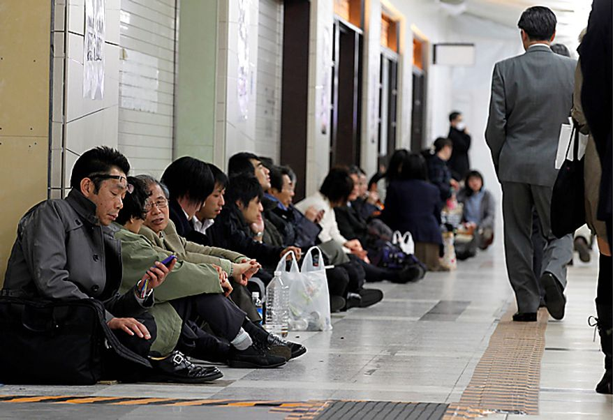 Stranded commuters sit inside Tokyo railway station as train services are suspended due to a powerful earthquake in Tokyo Friday, March 11, 2011. The largest earthquake in Japan's recorded history slammed the eastern coasts Friday. (AP Photo/Hiro Komae)