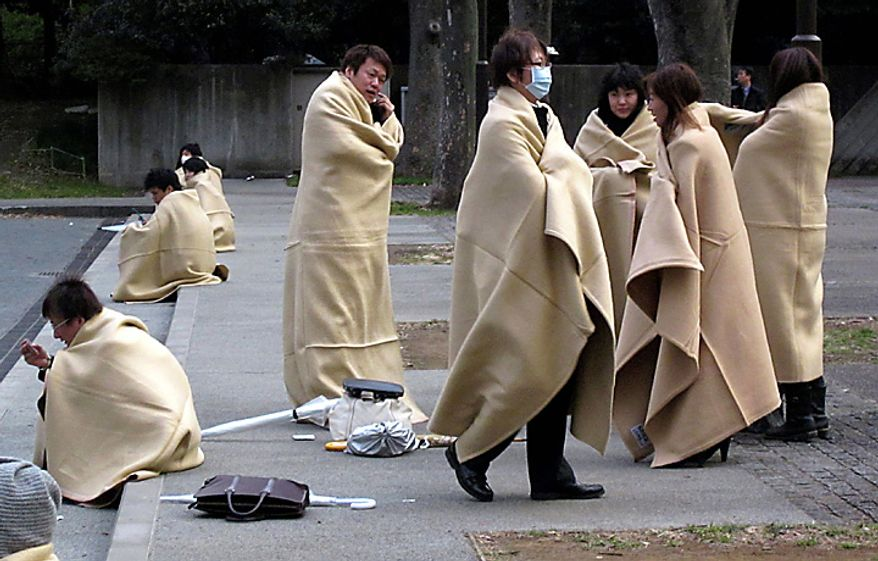 Stranded commuters wrap themselves in blankets bracing for chilly evening at a park in Yokohama, near Tokyo, following a strong earthquake hit eastern Japan on Friday, March 11, 2011. (AP Photo/Shuji Kajiyama)