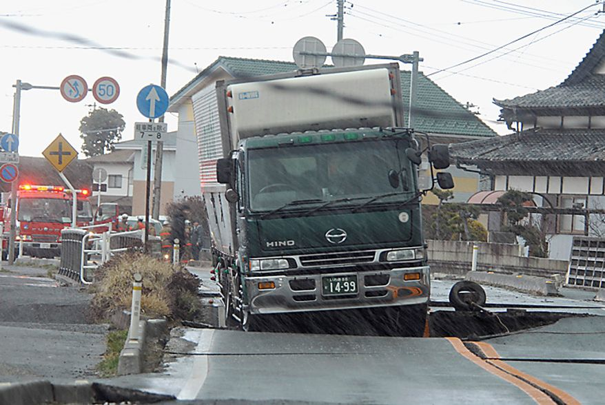 A truck remains stranded on a road damaged by a powerful earthquake in Iwaki city, Fukushima prefecture (state), Japan, Friday, March 11, 2011. The largest earthquake in Japan's recorded history slammed the eastern coast Friday. (AP Photo/Kyodo News)