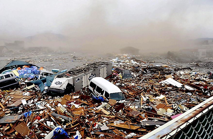 Cars and other Debris swept away by tsunami tidal waves are seen in Kesennuma in Miyagi Prefecture, northern Japan, after strong earthquakes hit the area Friday, March 11, 2011. (AP Photo/Keichi Nakane, The Yomiuri Shimbun)