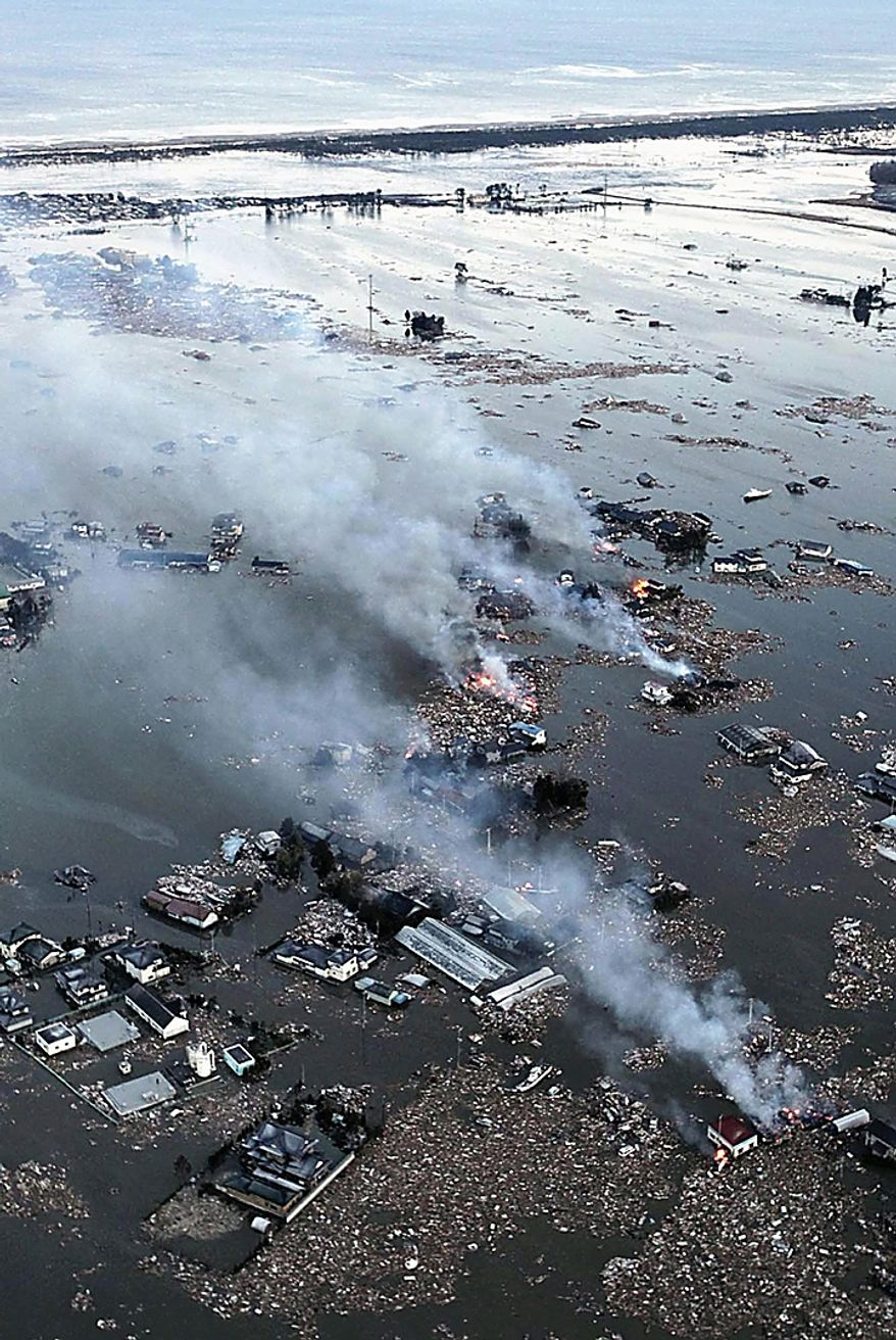 An aerial view shows houses burning and the Natori River flooded over the surrounding area in Natori, northern Japan, Friday, March 11, 2011. The largest earthquake in Japan's recorded history slammed the eastern coasts Friday. (AP Photo/Yasushi Kanno, The Yomiuri Shimbun)