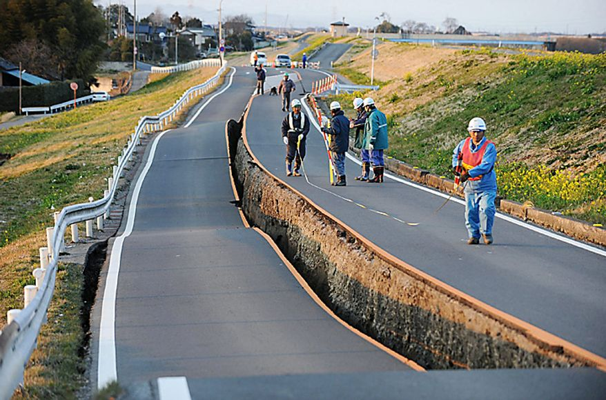 Workers inspect a caved-in section of a prefectural road in Satte, Saitama Prefecture, after one of the largest earthquakes ever recorded in Japan slammed its eastern coast Friday, March 11, 2011. (AP Photo/Saitama Shimbun via kyodo News)